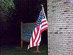 The US Flag waves under a bright light and in front of the New Horizons School sign.